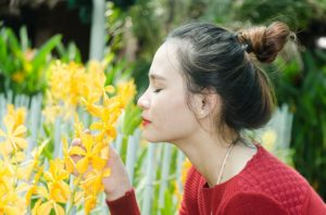 singaporean girl smelling orchid in garden